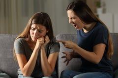 Mujer enojada que regaña a su amigo triste Imagen de archivo