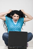 Mujer enojada que saca el pelo delante de la computadora portátil Fotografía de archivo libre de regalías