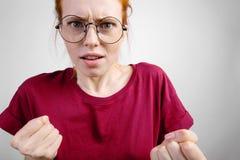 Mujer enojada que se coloca con los nudillos aumentados en el fondo blanco Imagen de archivo libre de regalías
