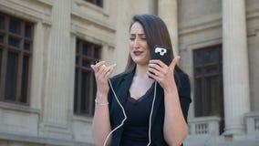 Mujer enojada y ansiosa joven que llora mientras que su teléfono apaga debido a la batería baja descargada en la ciudad almacen de metraje de vídeo