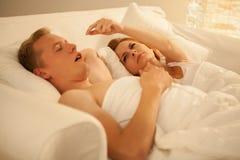 Mujer enojada y su marido que ronca Imagen de archivo libre de regalías