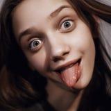 Mujer enrrollada joven que muestra su lengua Imagenes de archivo