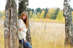 Mujer entre abedules en el otoño Imagen de archivo libre de regalías