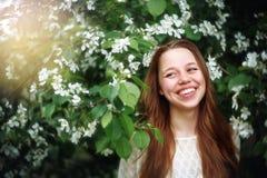 Mujer entre las flores de la primavera en la naturaleza Imagen de archivo libre de regalías