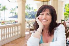 Mujer envejecida centro atractivo que se relaja en un patio tropical fotos de archivo