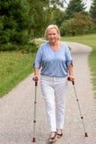 Mujer envejecida centro que camina con dos bastones imagenes de archivo