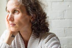 Mujer envejecida centro que parece pensativa Imagen de archivo libre de regalías