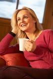 Mujer envejecida centro que se relaja con la bebida caliente en el sofá imagen de archivo libre de regalías