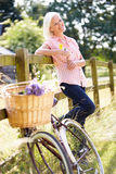 Mujer envejecida centro que se relaja en paseo del ciclo del país Imagen de archivo libre de regalías