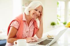 Mujer envejecida centro que usa el ordenador portátil sobre el desayuno Imágenes de archivo libres de regalías
