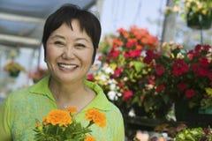 Mujer envejecida centro sonriente con las flores en cuarto de niños de la planta Imagen de archivo