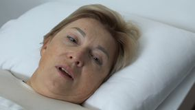 Mujer envejecida Disappointed que miente en la cama, cara de cierre con la mano de temblor, crisis almacen de metraje de vídeo