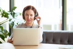 Mujer envejecida en auriculares y ordenador portátil en la tabla imagen de archivo
