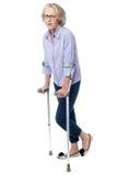 Mujer envejecida en dolor que camina con las muletas Foto de archivo
