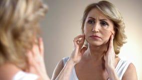 Mujer envejecida infeliz que mira en espejo en casa, tocando la cara, proceso de envejecimiento imagen de archivo libre de regalías
