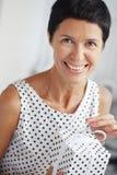 Mujer envejecida media con un regalo Imagenes de archivo