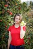 Mujer envejecida media en la camiseta roja que sostiene manzanas verdes en el jardín fotos de archivo