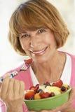 Mujer envejecida media que come la ensalada de fruta fresca Imágenes de archivo libres de regalías
