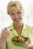 Mujer envejecida media que come la ensalada fresca Fotografía de archivo
