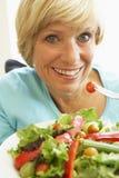 Mujer envejecida media que come la ensalada sana Foto de archivo