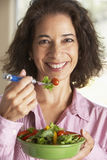 Mujer envejecida media que come una ensalada Imágenes de archivo libres de regalías