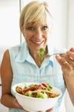 Mujer envejecida media que come una ensalada sana Foto de archivo libre de regalías