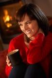 Mujer envejecida media que se relaja con la bebida caliente Imagen de archivo