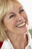 Mujer envejecida media que sonríe alegre Imágenes de archivo libres de regalías