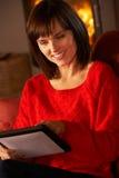 Mujer envejecida media que usa el ordenador de la tablilla Imágenes de archivo libres de regalías