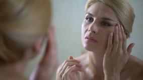 Mujer envejecida media triste decepcionada por la condición de la cara, primero arrugas, envejeciendo almacen de video