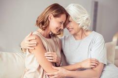 Mujer envejecida positivo y su abarcamiento de la hija Imágenes de archivo libres de regalías