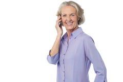 Mujer envejecida que asiste a llamada de teléfono Imágenes de archivo libres de regalías
