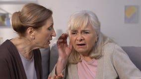 Mujer envejecida que grita al sufrimiento del amigo de la enfermedad de la pérdida de oído, sordera almacen de video