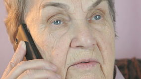 Mujer envejecida que habla en smartphone móvil seriamente almacen de metraje de vídeo