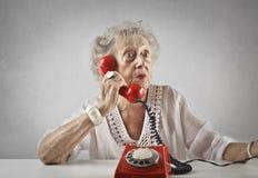 Mujer envejecida que habla en un teléfono del vintage imagenes de archivo