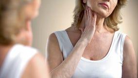 Mujer envejecida que mira en espejo la piel arrugada, pensando en cirugía plástica fotos de archivo libres de regalías