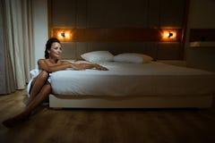 Mujer envuelta en cama siguiente que se sienta de la toalla de baño imagen de archivo libre de regalías
