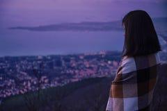 Mujer envuelta en la tela escocesa que mira la ciudad por la tarde imagen de archivo libre de regalías