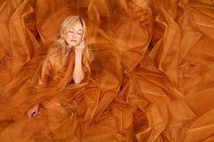 Mujer envuelta en tela que fluye del cobre Imagenes de archivo