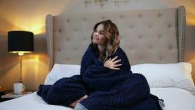 Mujer envuelta en una manta azul El sentarse acogedor en la cama y sonrisa metrajes