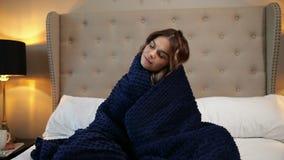 Mujer envuelta en una manta azul El sentarse acogedor en la cama y sonrisa almacen de metraje de vídeo