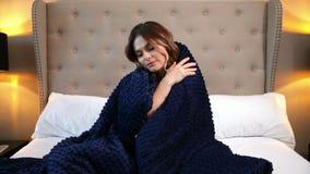 Mujer envuelta en una manta azul El sentarse acogedor en la cama y sonrisa almacen de video