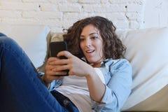 Mujer española atractiva joven que usa el teléfono móvil app o mandando un SMS en el sofá casero Fotografía de archivo libre de regalías