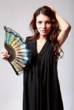 Mujer española con una fan y un vestido negro Fotos de archivo