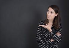 Mujer española joven que presenta con la mano en la pizarra fotografía de archivo