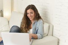 Mujer española atractiva joven que usa el ordenador portátil que sienta el trabajo relajado en el sofá casero Imagenes de archivo