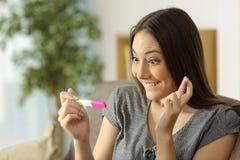 Mujer esperanzada que comprueba una prueba de embarazo Imagen de archivo