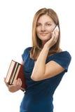 Mujer-estudiante con los libros que habla encendido Fotografía de archivo libre de regalías