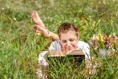 Mujer-estudiante joven hermoso que lee un libro que miente en la hierba Muchacha bonita al aire libre en verano Imágenes de archivo libres de regalías