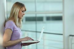 Mujer estudiosa que usa el ordenador portátil Fotos de archivo libres de regalías